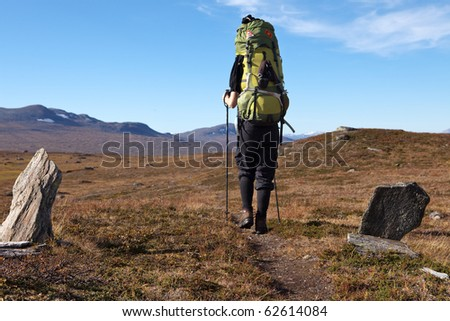 female hiker with huge backpack on tour in Laponia - stock photo