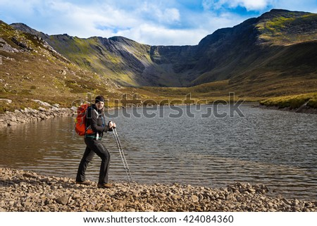 Female hiker with trekking poles and backpack posing lake side with the Macgillycuddy's Reeks  mountain range in the background