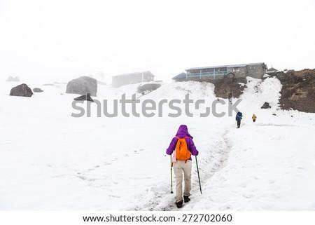 Female hiking on snow trail towards base camp - stock photo