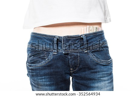 Female hips in blue jeans with money in belt.