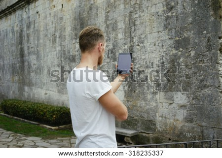 Female hipster using digital tablet on the background of the medieval walls
