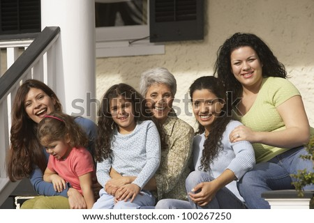 Female Hispanic family members sitting on the porch smiling