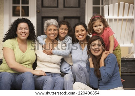 Female Hispanic family members sitting on the porch smiling - stock photo