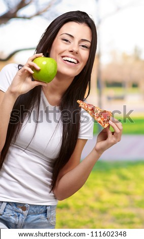Female Holding A Piece Of Pizza And A Apple, Outdoor