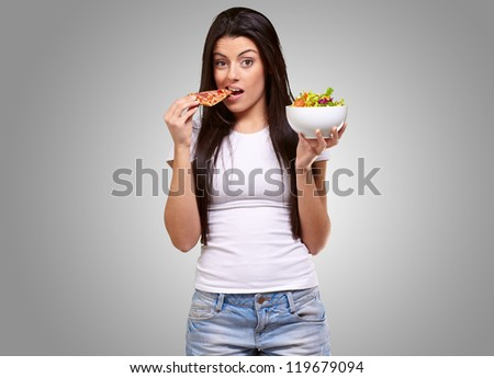 Female Holding A Piece Of Pizza And Salad Bowl On Gray Background