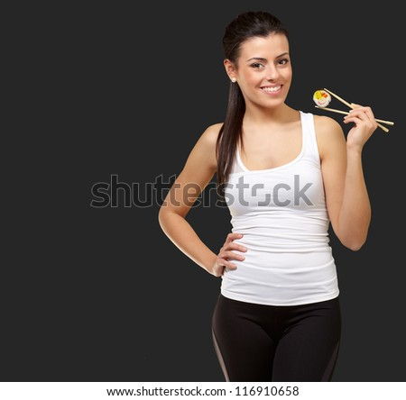 Female Holding A Sushi With Chopstick On Black Background
