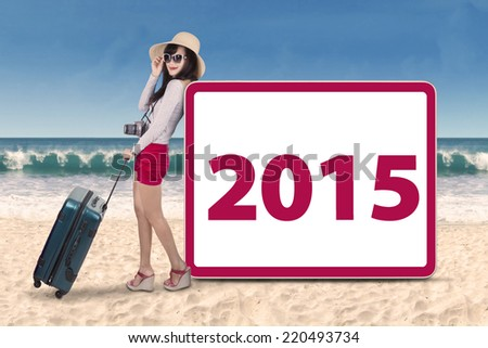 Female holding bag on beach and leans to a board with number 2015 - stock photo