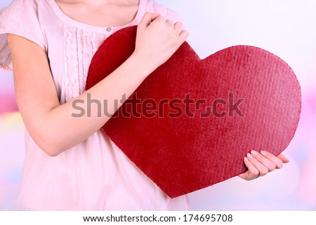 Female holding big red heart on bright background - stock photo