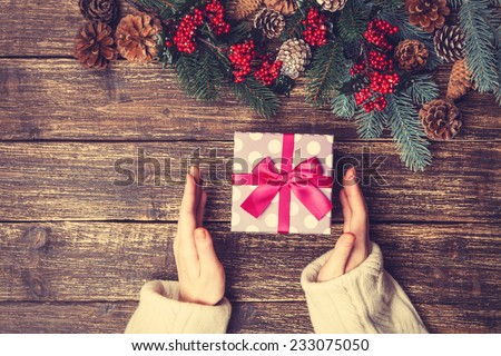 Female holding gift box on a table. - stock photo