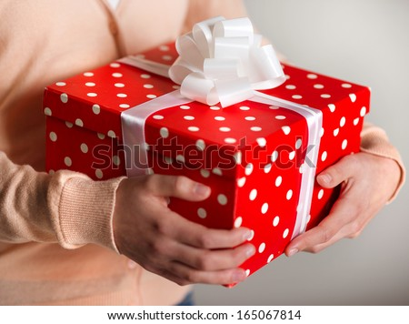 Female holding gift box with ribbon in her hands