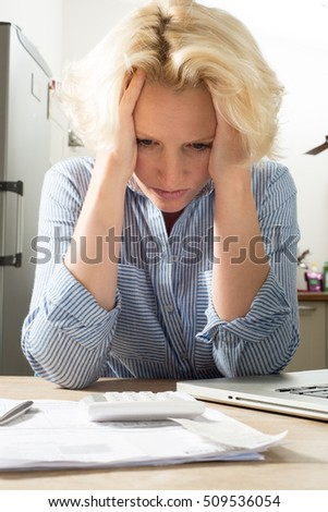 Female holding head in hands in despair whilst doing accounts