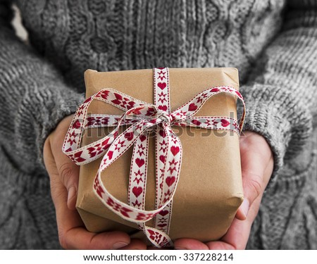 Female Holding Rustic Decorated Christmas Gift with Red and White Ribbon - stock photo