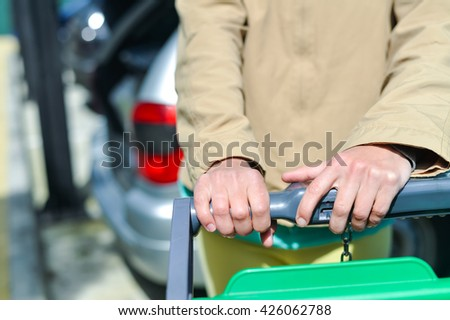 Female holding shopping push cart closeup picture of hands with car on background - stock photo