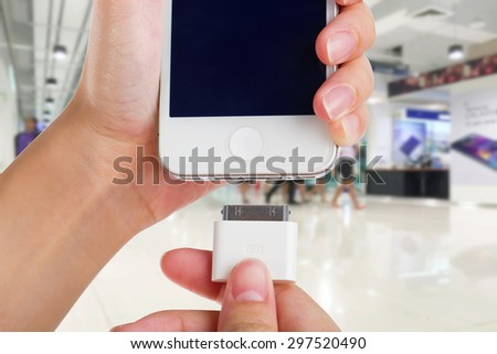Female holding USB port charger connect to smart phone. - stock photo