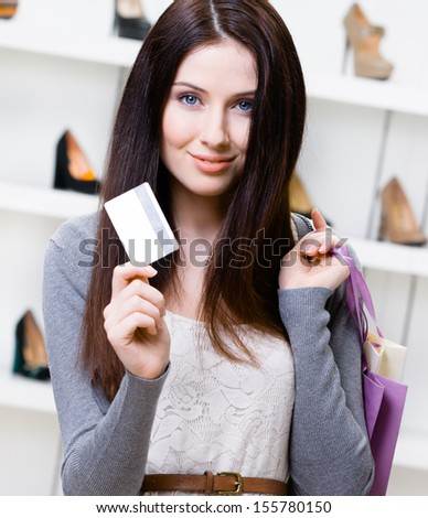 Female holds credit card in footwear shop with great variety of stylish shoes