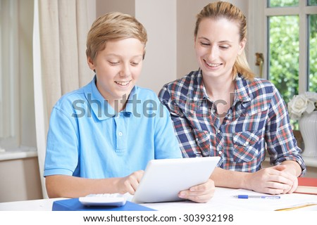 Female Home Tutor Helping Boy With Studies Using Digital Tablet - stock photo