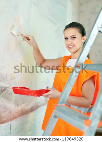 Female house painter paints wall with brush - stock photo