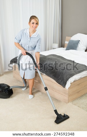 Female Housekeeper Cleaning Rug With Vacuum Cleaner In Hotel Room