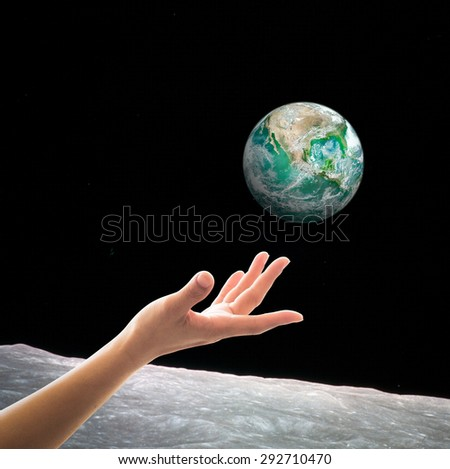 Female human hand reaching green planet (View of green earth from the moon): Green globe view from out of space: Save green environment concept: Elements of this image furnished by NASA  - stock photo