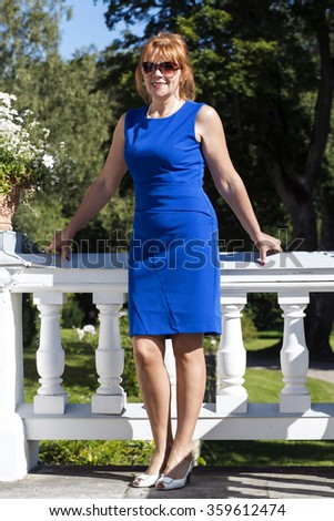 Female in a blue dress poses elegantly - stock photo