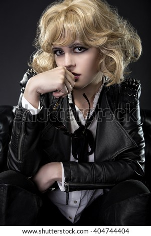 Female in black leather and shades posing arrogantly like a famous rockstar.  Her fashion style shows attitude and a sassy subculture. - stock photo