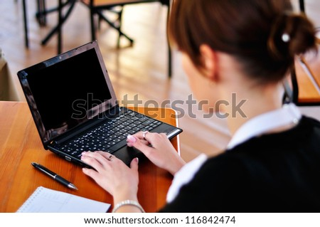 Female in black using laptop, have notepad and pen at the table - stock photo