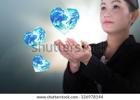 female in business uniform holding global earth floating over blurred light background in love earth concept Elements of this image furnished by NASA