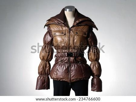 female in coat on mannequin-light background - stock photo