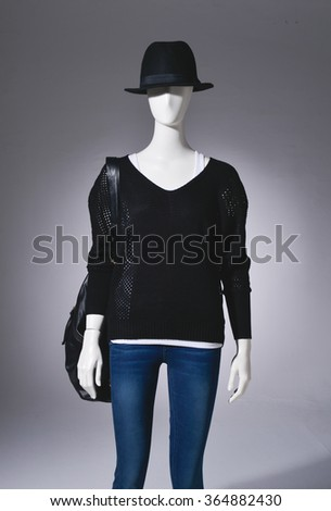 female in hat with bag on mannequin in light background - stock photo