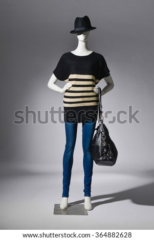 female in jeans with bag on a mannequin-light background    - stock photo