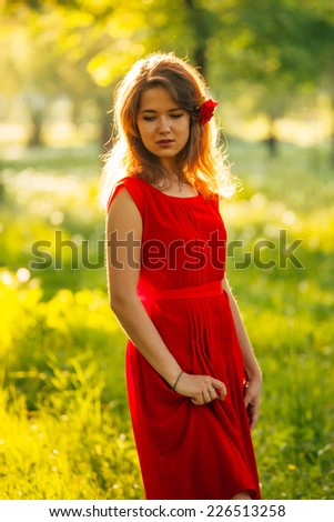Female in red dress walking in the autumn  forest - stock photo