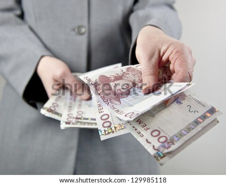 Female in suit handing over some swedish 500 notes - stock photo
