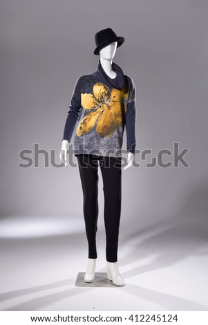 female in sweater with hat on mannequin in light background - stock photo