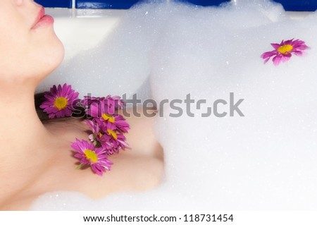 Female in the bath with the flowers - stock photo
