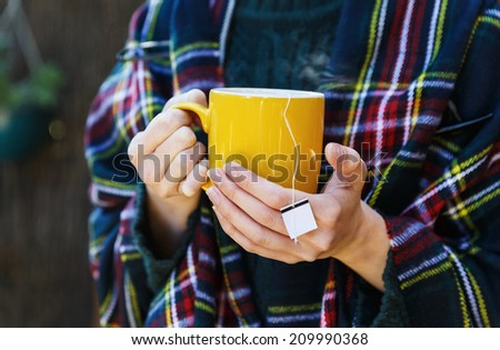 Female in warm clothing holding cup of hot tea. Selective focus, shallow Depth of Field - stock photo