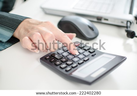 Female index finger typing on a calculator, closeup - stock photo