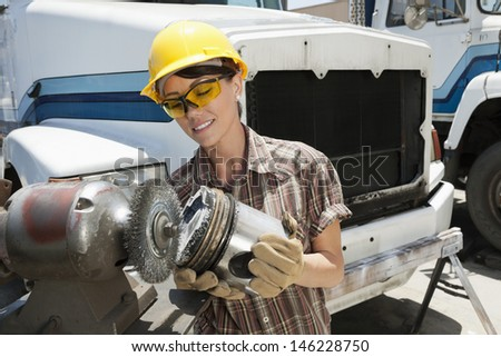 Female industrial worker buffing a truck engine cylinder - stock photo