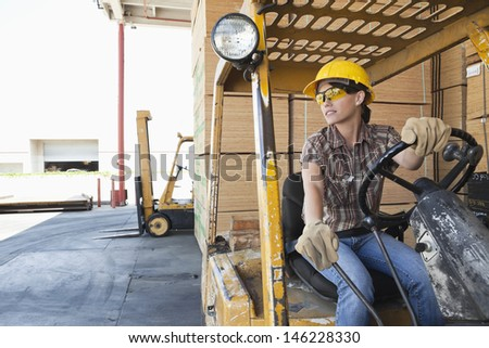 Female industrial worker looking away while driving forklift truck - stock photo