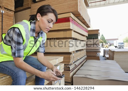Female industrial worker using cell phone while sitting on stack of wooden planks - stock photo