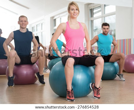 Female instructor showing exercise on fitness ball