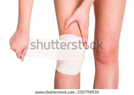 Female is wrapping her knee injury with bandage. - stock photo