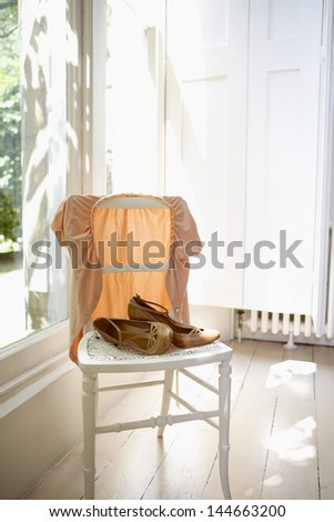 Female jacket and shoes on chair by window - stock photo