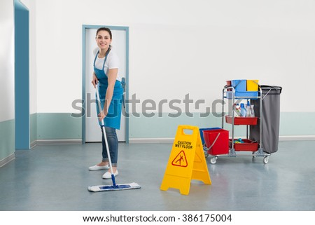 Female Janitor Mopping Corridor With Caution Sign - stock photo