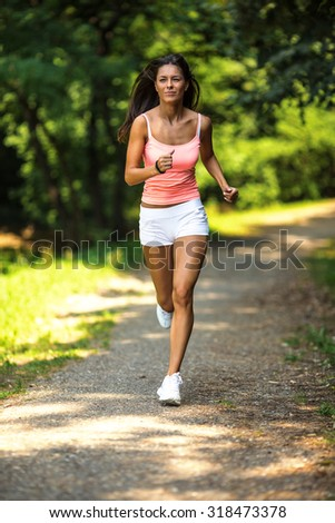 Female jogger running at the park.Green nature environment.