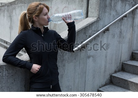 Female jogger standing by the stairs drinking water - stock photo