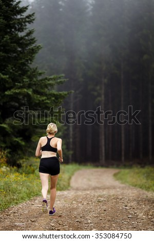 Female Jogger Training in Forest early in the Morning on a Foggy day of Autumn or Spring - stock photo