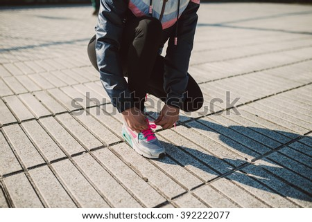 Female jogger tying her running shoes preparing for a jog outdoors