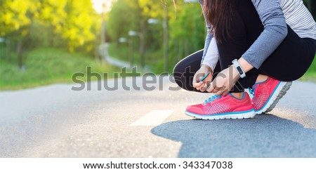 Female jogger tying her shoes preparing for a run - stock photo