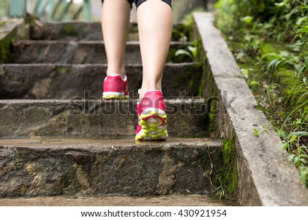 Female jogging up the stairs in the park outside