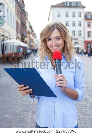 Female journalist with microphone in the city - stock photo